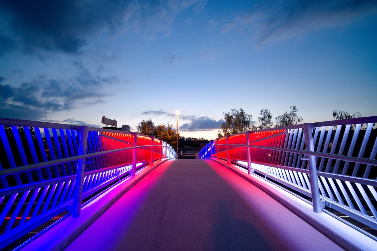 Moderní RGB LED designové osvětlení zasazené přímo do umělecky pojatého zábradlí na lávce pro pěší přes dálnici D5.